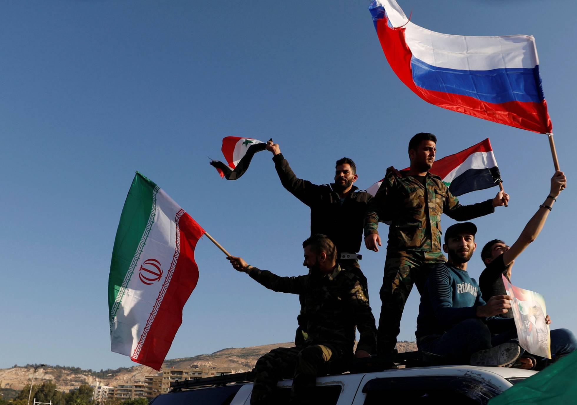 Tropas sirias con banderas de Rusia e Irán